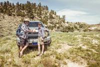 Portrait of man and teenage son on hiking road trip leaning on car hood in landscape, Bridger, Montana, USA