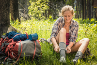 Teenage girl hiker putting on sock in forest, Red Lodge, Montana, USA