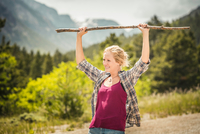 Teenage girl hiker holding up walking stick on rural road, Red Lodge, Montana, USA