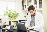 Scientist typing on laptop in laboratory at plant growth research facility 11015272919| 写真素材・ストックフォト・画像・イラスト素材|アマナイメージズ