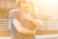 Young couple hugging in sunlight