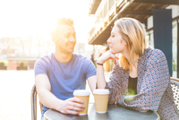 Young couple sitting at sidewalk cafe with disposable cups face to face smiling