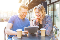 Young couple sitting at sidewalk cafe with disposable cups using digital tablet smiling
