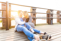 Young couple leaning against railings hugging, face to face smiling