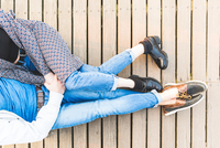 Overhead view of young couple from chest down sitting on wooden decking holding hands