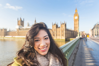 Portrait of young woman on Westminster bridge looking at camera smiling, Thames river, London, UK