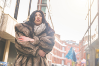 Low angle view of young woman in street wrapped in fur coat looking away, London, UK