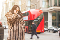 Young woman in street wearing fur coat making telephone call looking away smiling, London, UK