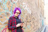 Woman using smartphone against graffiti wall