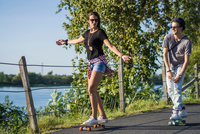 Young couple skateboarding in park