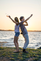 Young couple back to back, raising arms by sea at sunset