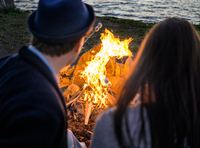 Young couple in front of campfire by sea