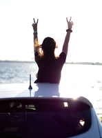 Young woman standing through sunroof by sea