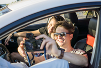 Happy young couple taking selfie in vehicle