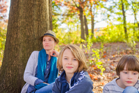 Mother and sons, sitting in forest