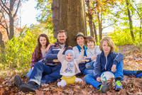 Portrait of family sitting in forest, beside tree