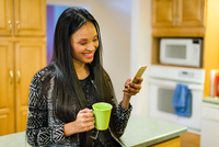 Young woman drinking coffee in kitchen whilst reading smartphone text