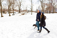Young couple strolling in snow with dog, Central Park, New York, USA