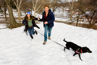 Young couple running with dog in snowy Central Park, New York, USA