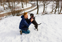 Young man petting dog in snowy Central Park, New York, USA