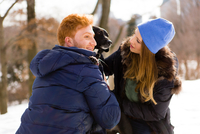 Young couple petting dog in snowy Central Park, New York, USA