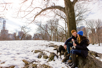Young couple sitting with dog and drink flask in snowy Central Park, New York, USA