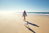 Mature woman with running dog on beach, Conil de la Frontera, Spain