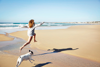 Mature woman and dog leaping over water on beach, Conil de la Frontera, Spain