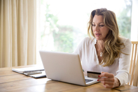 Mature woman using credit card with laptop at home