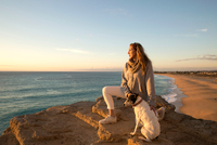 Mature woman and dog looking out to sea from cliff rock, Conil de la Frontera, Spain