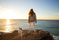 Rear view of woman and dog watching sunset from cliff rock, Conil de la Frontera, Spain
