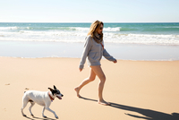 Bare legged woman wearing hoody walking with dog on beach, Conil de la Frontera, Spain