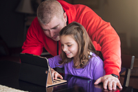 Father and daughter using wireless digital tablet at home