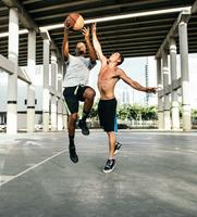 Men on basketball court jumping for basketball