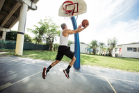 Side view of young man on basketball court in mid air holding basketball jumping for hoop