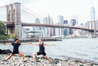 Two men practicing yoga on riverside in front of Brooklyn Bridge, New York, USA