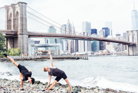 Two men doing yoga on riverside in front of Brooklyn Bridge, New York, USA