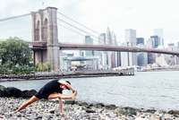 Young man practicing yoga on riverside in front of Brooklyn Bridge, New York, USA