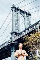 Man meditating with hands together in front of Manhattan Bridge, New York, USA