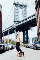 Young man doing yoga handstand in front of Manhattan Bridge, New York, USA