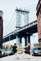 Two men leaning sideways in yoga position in front of Manhattan Bridge, New York, USA