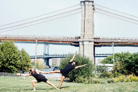 Two men leaning sideways in yoga foot hold position in front of Brooklyn Bridge, New York, USA