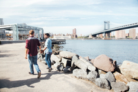 Rear view of male couple strolling on riverside by Manhattan Bridge, New York, USA