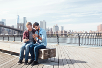 Male couple sitting on riverside by Brooklyn Bridge reading smartphones, New York, USA