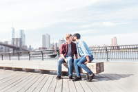 Male couple kissing on riverside by Brooklyn Bridge, New York, USA
