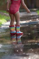 Child in wellies playing in puddle of water