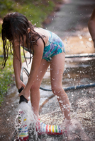 Girl filling wellies with water from hose