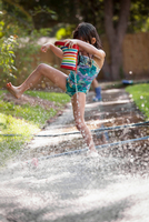 Girl holding welly, jumping over puddle of water on sidewalk