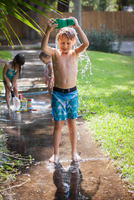 Boy pouring water from welly over head on sidewalk
