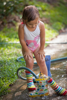 Child filling wellies with water from hose